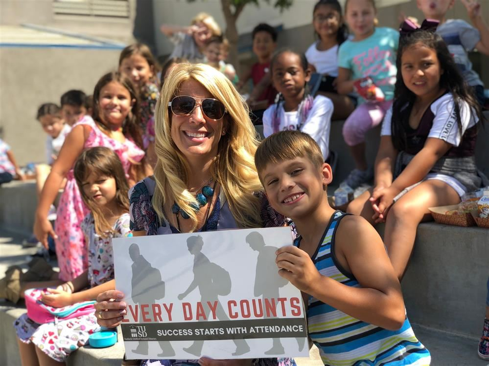 Principal Nicole Aviles with Every Day Counts Sign